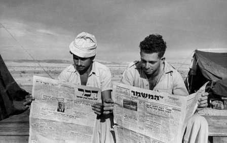 "Kibbutz members reading ""Al HaMishmar"" and ""Davar"" newspapers, 1949 (PHKH\1279884)"