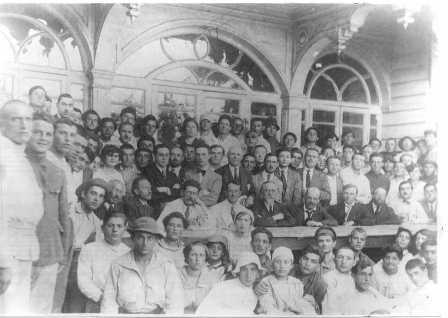 Druyanow (fourth from left in the row in front of the table) and a group of Russian writers